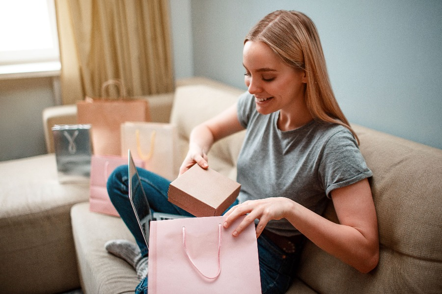 A woman opens boxes and bags at home after online shopping